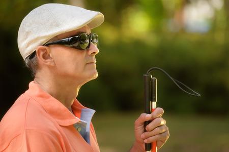 Spaanse blinde man, latino mensen met een handicap, gehandicapte persoon en het dagelijks leven. Visueel gehandicapte man met wandelstok, zittend op een bankje in het stadspark. Ruimte kopiëren Stockfoto