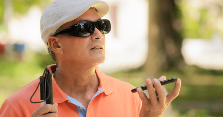 Spaanse blinde man met een handicap. Visueel gehandicapte man met behulp van Digital Assistant en Ease of Access functies op de mobiele telefoon, spraak typen naar smartphone Stockfoto