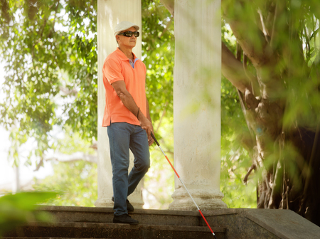 ヒスパニック盲目人、ラテン系アメリカ人、障害者障害者と日常。都市公園における手順を降順、杖を持つ視覚障害者男 写真素材