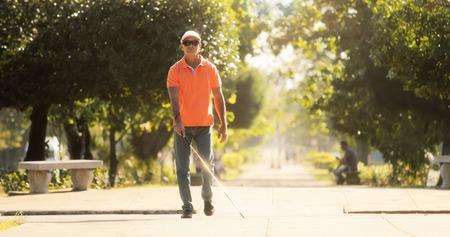 Spaanse blinde man, Latino mensen met een handicap, gehandicapte persoon en dagelijks leven. Zichtgestoorde man met stokje, over de straat.