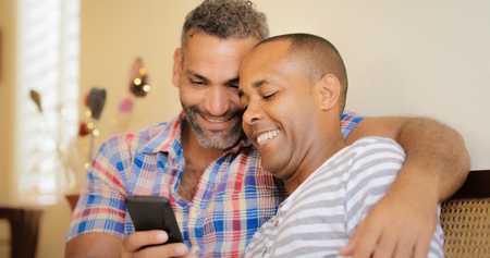 adult sex: Homosexual couple, gay hispanic men watching media on mobile phone, sitting on sofa at home. Stock Photo