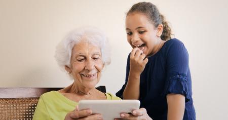 祖母と孫娘の家族関係は。絆、愛情とタブレットを自宅で Web をサーフィン愛、おばあちゃんと女性の孫。