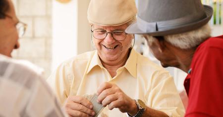 Gelukkige actieve gepensioneerden, oude Spaanse vrienden met plezier, senioren speelkaarten thuis.