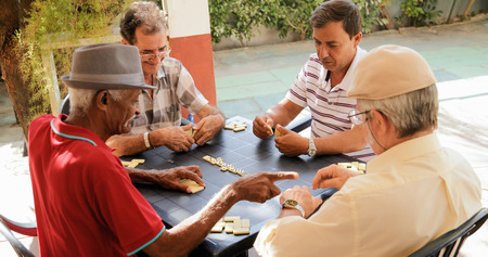 Retired people, seniors and free time. Old latino men having fun and playing game of domino in Cuba. Archivio Fotografico