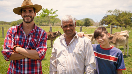 Everyday life for farmers with cows in the countryside. Peasants work in Latin America with livestock in family country ranch. Portrait of happy grandfather, dad and child smiling.