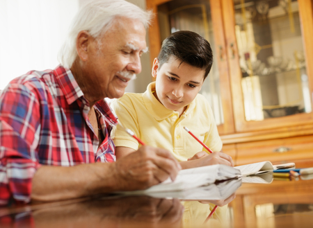 Little Boy Doing School Homework With Old Man At Home