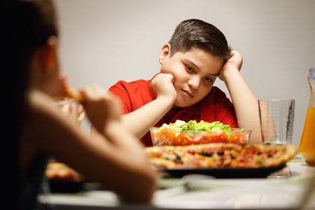 Mother Giving Salad Instead Of Pizza To Overweight Son