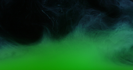 Green Ink Colors in Water Creating Liquid Art Shapes Stock Photo