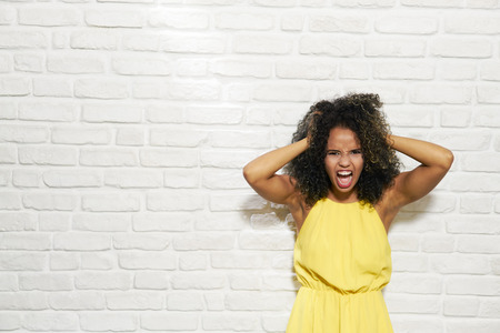 Facial Expressions Of Young Black Woman On Brick Wall Stock Photo