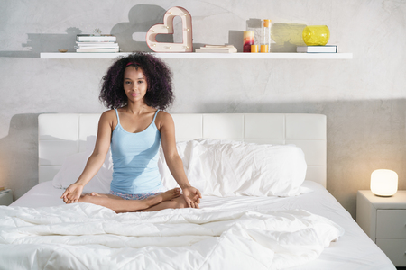 Young African American Woman Doing Yoga In Bed After Sleep Stock fotó - 100962329