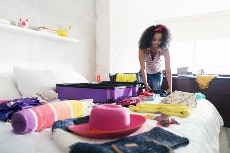 Pretty Young Black Woman Packing Bags For Holidays Standard-Bild