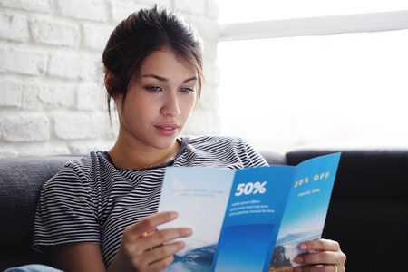 Woman Reading Travel Flye On Sofa At Home