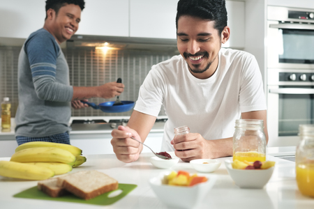 Homosexual Couple Eating Breakfast Cooking In Kitchen