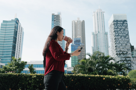 Chinese Woman With Phone Walking And Drinking Coffee 免版税图像 - 108417261