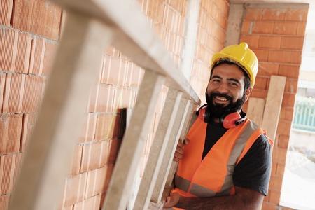 Ritratto di felice lavoratore ispanico sorridente in cantiere