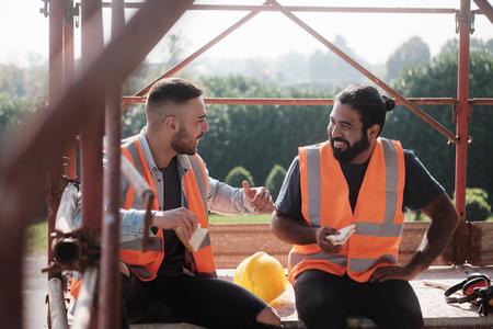 Travailleurs heureux dans le chantier de construction pendant la pause déjeuner Banque d'images