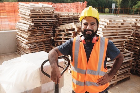 Happy Hispanic Manual Worker With Forklift Smiling At Camera Stock Photo