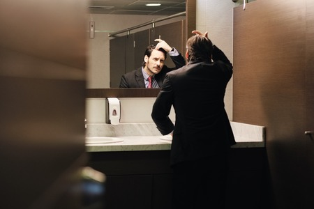 Worried Hispanic Business Man Looking At Hairline In Office Restrooms Banque d'images