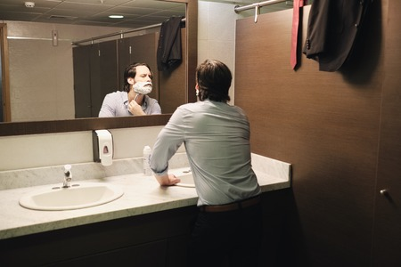 Business Man Shaving In Office Bathroom After Early Morning Commute