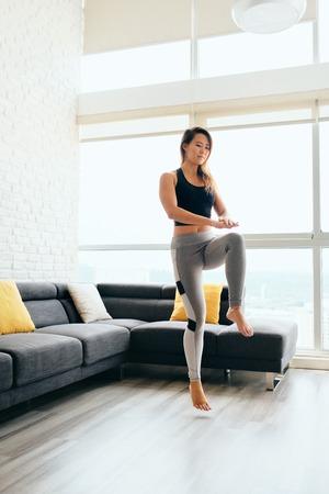 Mujer adulta entrenando ABS y piernas haciendo toques de rodilla altos Foto de archivo