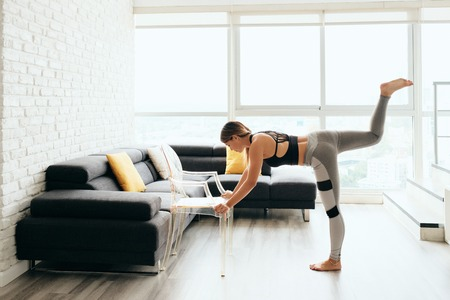 Adult Woman Training Body By Raising Legs Using Chair