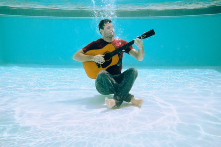 Young Man Playing Music With Guitar And Singing Song Underwater Stock Photo