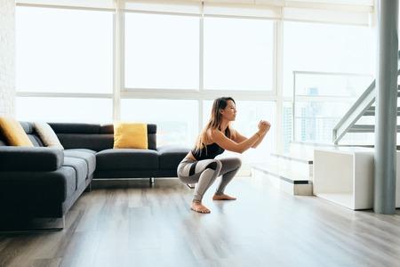 Volwassen vrouw die benen traint en squat in en uit doet