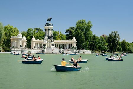 People in Parque del Retiro rowing on boats