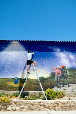 Man Painting Graffiti Along The Camino de Santiago Standard-Bild - 134363497