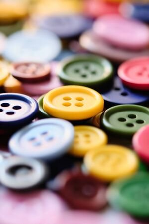 Large Group Of Colorful Plastic Sewing Buttons On a Table, Randomly Arranged With Narrow Focus