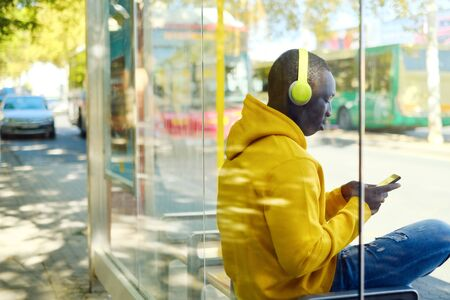 African Young Man Listening To Music At Bus Stop