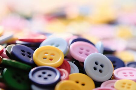 Large Group Of Colorful Plastic Sewing Buttons On a Table, Randomly Arranged With Copy Space For Text