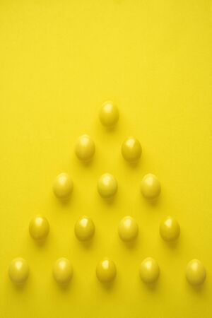 Pattern Of Chicken Eggs In Pyramid Shape Against Yellow Background