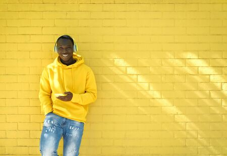 African Young Man Listening Music Leaning On Yellow Wall