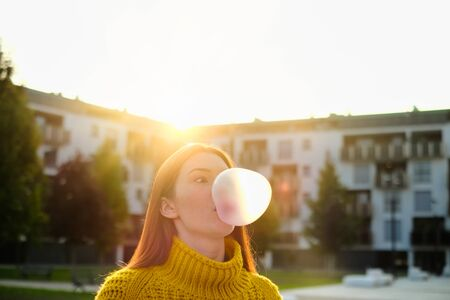 Young Woman Chewing Gum And Making Big Balloon