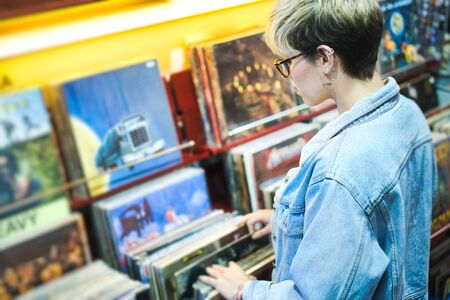 Young Woman Choosing Vintage Vinyl LP In Records Shop Фото со стока - 139491268