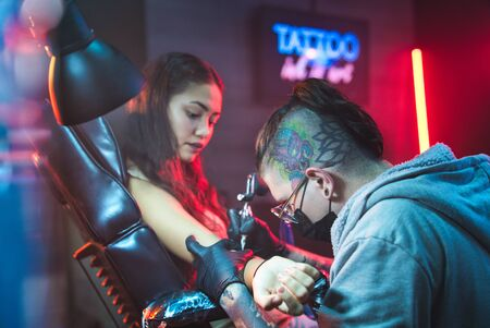 Young Woman Getting Tattoos In Beauty Parlor With Tattooist Working