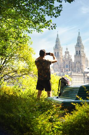 Male Pilgrim Taking A Picture Of The Cathedral With Mobile Phone In Santiago De Compostela, Spanish Town At The End Of The Way Of St James.