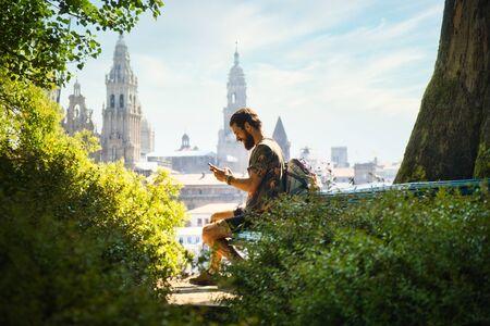 Pèlerin mâle tapant un message sur téléphone mobile à Santiago de Compostela, ville espagnole à la fin du chemin de Saint-Jacques, avec la cathédrale en arrière-plan. Banque d'images