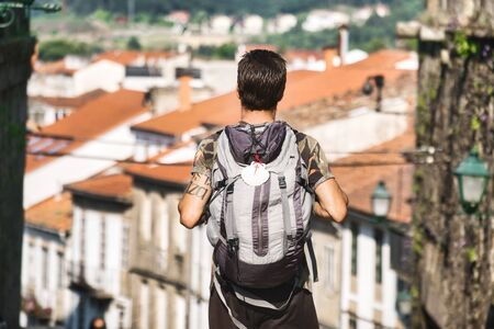 Male Pilgrim Walking In Santiago de Compostela, The End Of The Way of Saint James, With The Iconic White Shell Hanging From His Backpack