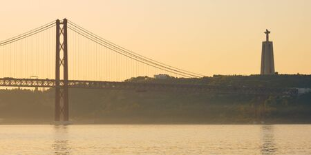 25th of April Suspension Bridge in Lisbon, Portugal, formerly known as Salazar bridge on Tagus River. Фото со стока