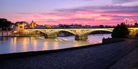 View Of Triana Bridge In Seville Spain At Sunset Фото со стока - 142185772