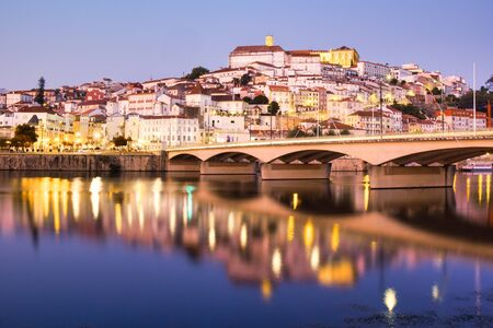 View Of Coimbra, One Of The Main Cities In Portugal, with Mondego River And University Buildings At Night.