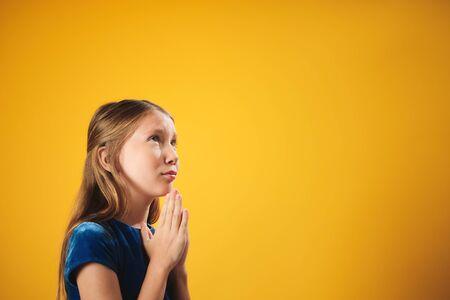 Portrait Of Caucasian Little Girl Praying God On Yellow Background