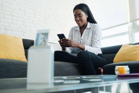 Mujer negra con impresora Wi-Fi portátil para imprimir imágenes Foto de archivo