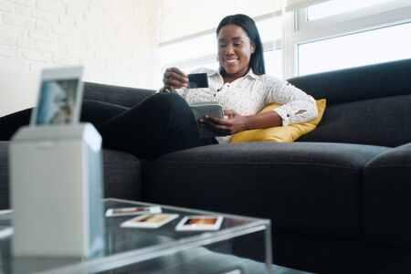 Black Woman Using Portable Printer For Printing Pictures