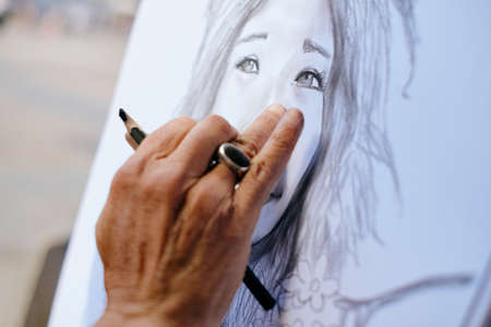 Street Painter Drawing Portrait Of Tourist With Charcoal