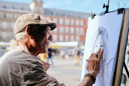 Old Male Street Painter Drawing Portrait Of Tourist