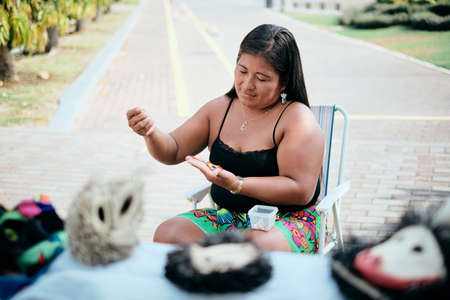 Indigenous Woman Beading Flower Coaster At Market Stall For Tourists
