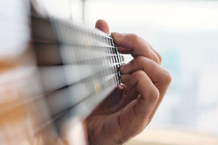 Close-up Of Man Practising Chords With Classical Guitar. Selective Focus